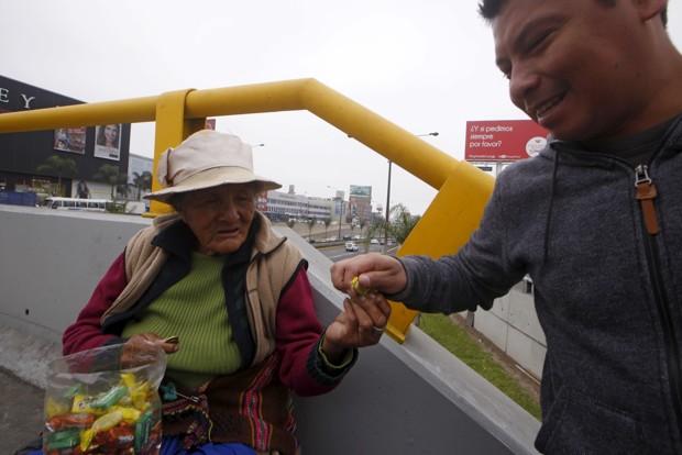 الخاندرا بالدینی 78 ساله روی پل هواییای در منطقهی سن بورخای لیما در پِرو، آبنبات میفروشد. (رویترز، Mariana Bazo)
