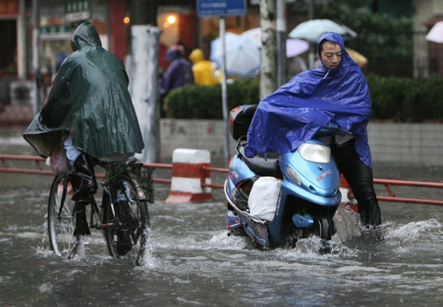 Shanghai residents struggle through flooded roads as a typhoon bears down on the city, 18 September 2007. China relocated hundreds of thousands of people as its most populous city Shanghai braced for Typhoon Wipha. The typhoon, packing winds of 180 kilometres (112 miles) an hour, was gaining strength and expected to make landfall in east China around midnight, after gale-force winds and driving rains first swipe northern Taiwan. AFP PHOTO/Mark RALSTON (Photo credit should read MARK RALSTON/AFP/Getty Images)