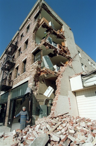"""A woman walks over rubble after taking some of her belongings from her Hollywood Boulevard apartement building that was destroyed in the Northridge earthquake, January 19, 1994, in Hollywood, California. The Northridge earthquake occurred on January 17, 1994 at 4:31 AM Pacific Standard Time in Reseda, a neighborhood in the city of Los Angeles, California. The earthquake had a """"strong"""" moment magnitude of 6.7, but the ground acceleration was the highest ever instrumentally recorded in an urban area in North America. (Photo credit should read TIMOTHY A. CLARY/AFP/Getty Images)"""