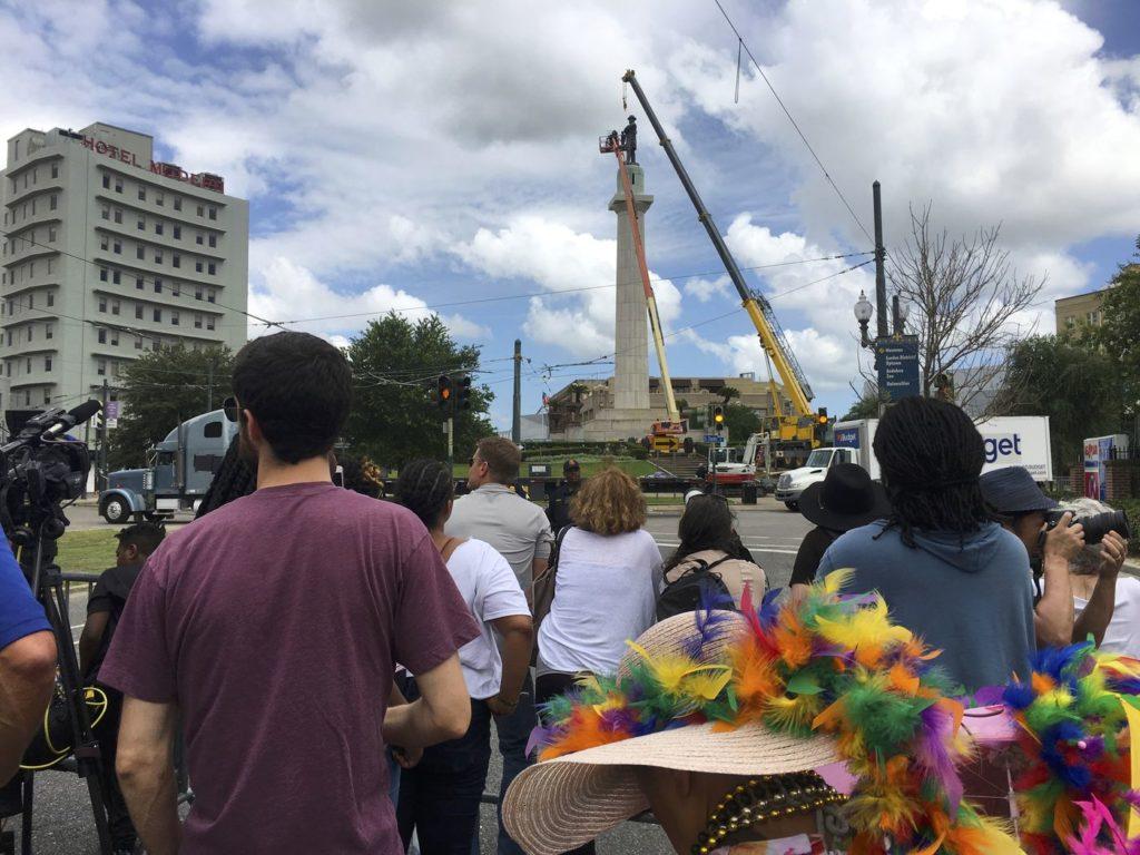 انبوهی از مردم در نیو اورلئان، می 2017، مشغول تماشای کارگران شهرداری هستند که با کمک جرثقیل برای برداشتن یکی از بناهای یادبود دولت موتلفه آمریکا تلاش میکنند.